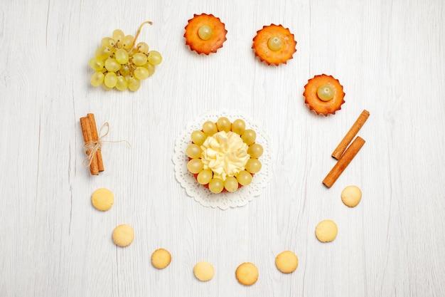 Vista de cima bolinhos saborosos com uvas e biscoitos em uma mesa branca.