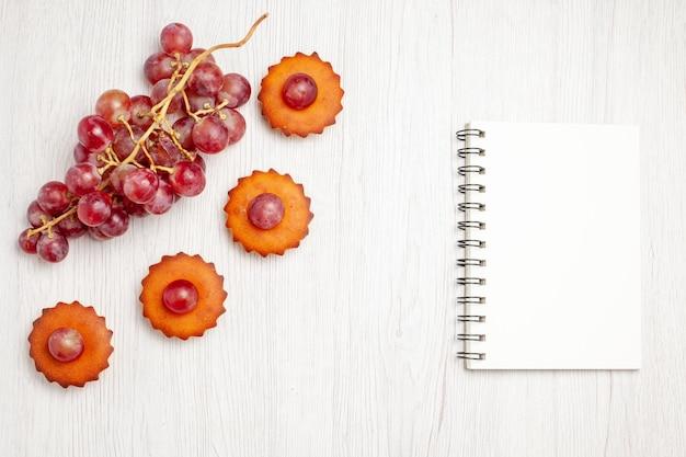 Vista de cima bolinhos saborosos com uvas frescas na superfície branca