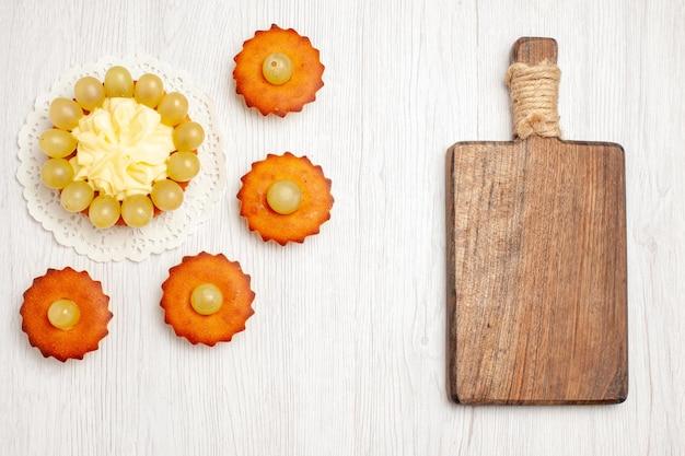Vista de cima bolinhos saborosos com uvas verdes na superfície branca frutas chá sobremesa biscoito biscoito torta de bolo
