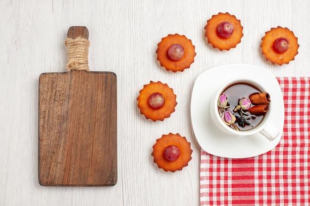 Vista de cima bolinhos saborosos com xícara de chá na mesa branca frutas chá sobremesa biscoitos bolachas torta de bolo