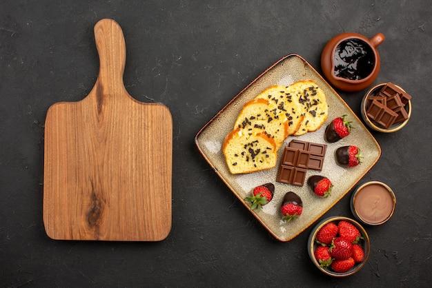 Vista de cima bolo apetitoso com morangos e chocolate entre tigelas de morangos com creme de chocolate e chocolate ao lado da tábua de madeira marrom