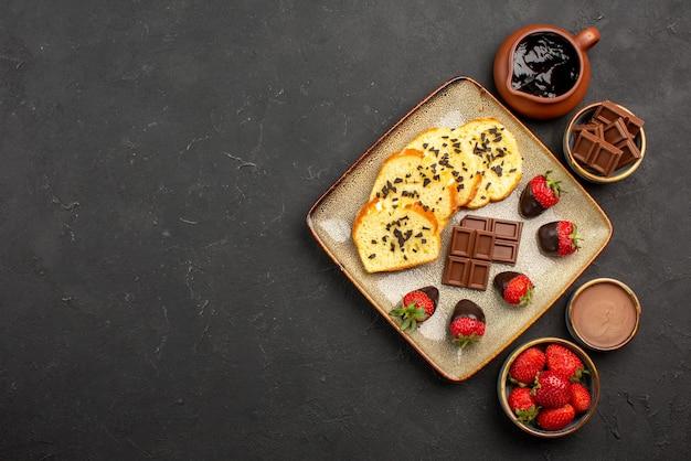 Vista de cima bolo apetitoso com morangos e chocolate entre tigelas de morangos com creme de chocolate e chocolate no lado direito da mesa preta