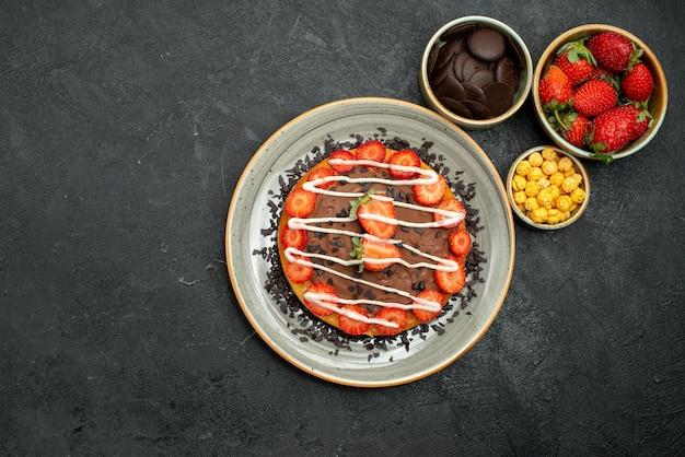 Vista de cima, bolo apetitoso com pedaços de chocolate e morango em um prato branco e tigelas de chocolate, morango e avelã no centro da mesa escura