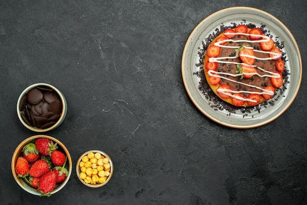 Vista de cima bolo apetitoso com pedaços de chocolate e morango no lado direito da mesa e tigelas de chocolate, morango e avelã no lado esquerdo da mesa escura