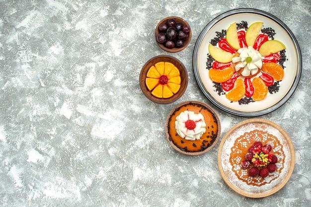 Vista de cima bolo cremoso com bolo de framboesa e torta na superfície branca fruta doce biscoito bolo torta açúcar