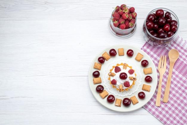 Vista de cima bolo cremoso com framboesas e biscoitos junto com cerejas na mesa de luz