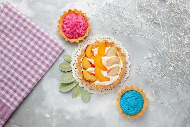 Vista de cima bolo cremoso com frutas fatiadas e creme branco junto com bolos cremosos em fundo claro bolo de frutas biscoito biscoito doce