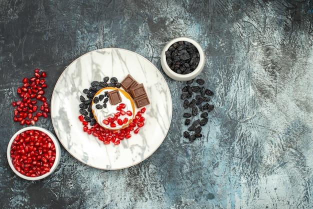 Vista de cima, bolo cremoso gostoso com romãs de chocolate e passas em fundo claro-escuro