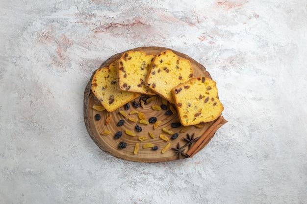 Vista de cima bolo de passas delicioso com frutas secas na superfície branca