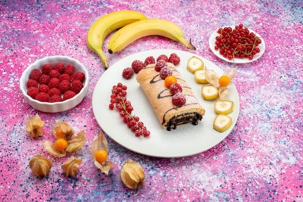 Vista de cima bolo de rolo com frutas bananas dentro de um prato branco no fundo colorido bolo de biscoito de cor doce
