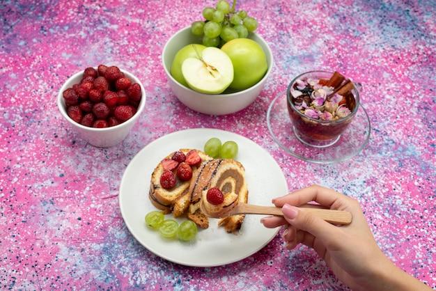 Vista de cima bolo de rolo dentro do prato com uvas e morangos junto com chá na mesa colorida bolo biscoito doce de frutas