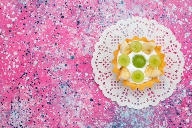 Vista de cima bolo delicioso com bananas e kiwis na superfície roxa açúcar doce fruta