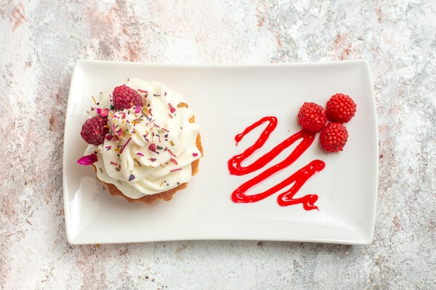 Vista de cima bolo delicioso com creme e framboesas no fundo branco bolo de chá biscoito doce creme sobremesa