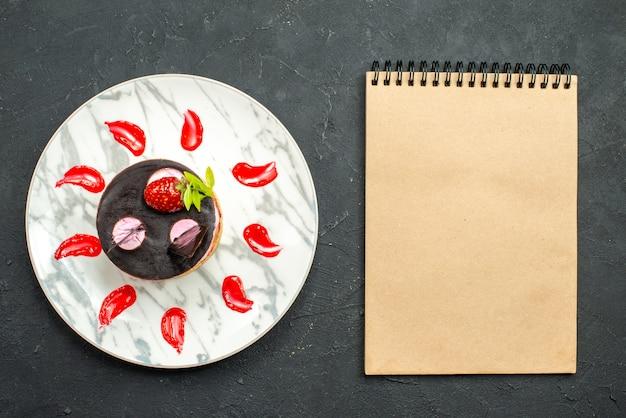 Vista de cima bolo delicioso com morango e chocolate em placa oval um caderno em fundo escuro