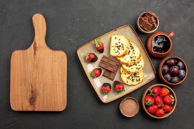 Vista de cima bolo e morangos bolo apetitoso com chocolate e morangos e tigelas com morangos, frutas vermelhas e calda de chocolate ao lado da placa de madeira