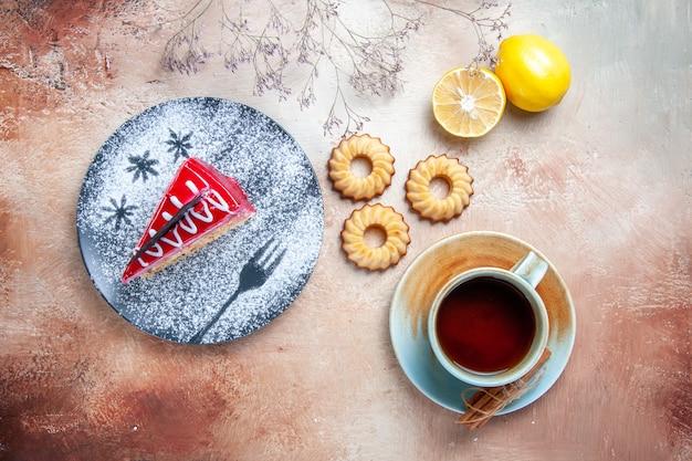 Vista de cima bolo um bolo apetitoso no prato uma xícara de chá, canela, biscoitos e limão