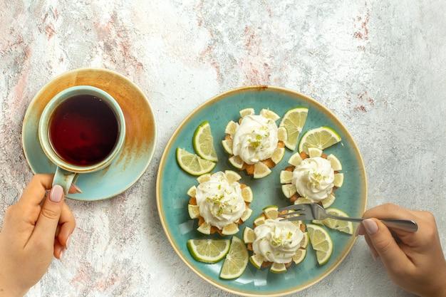 Vista de cima bolos cremosos deliciosos com rodelas de limão e xícara de chá na superfície branca bolo biscoito biscoito creme chá doce
