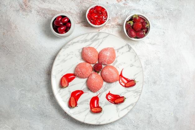 Vista de cima bolos de morango rosa pequenos doces deliciosos na mesa branca biscoito açúcar chá doce biscoitos bolo
