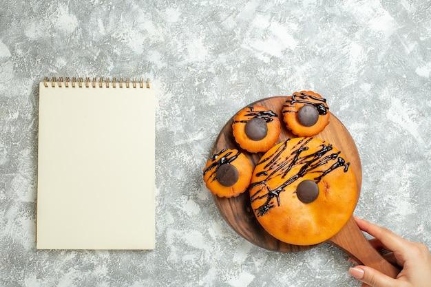 Vista de cima bolos deliciosos com chocolate e cobertura no bolo de superfície branca torta de biscoito de cacau bolo de sobremesa