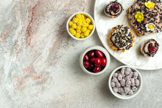 Vista de cima, bolos deliciosos e cremosos com doces na superfície branca clara, bolo de chá, biscoito doce de aniversário
