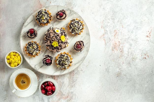 Vista de cima, bolos deliciosos e cremosos com fatias de chocolate na superfície branca, bolo de chá, biscoito doce, biscoito de aniversário, creme
