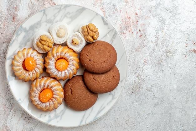 Vista de cima bolos diferentes docinhos em fundo branco claro biscoito biscoito açúcar chá doce bolo