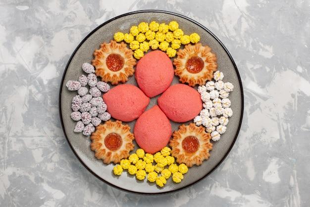 Vista de cima bolos rosa com doces e biscoitos dentro do prato na superfície branca doce assar bolo biscoito biscoito de torta de chá