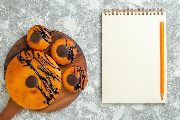 Vista de cima bolos saborosos com chocolate e cobertura na superfície branca torta de biscoito de cacau bolo de sobremesa bolo doce