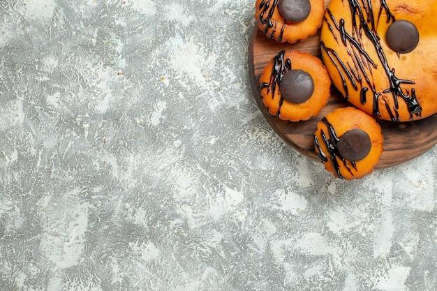 Vista de cima bolos saborosos com chocolate e cobertura no chão branco torta sobremesa bolo cacau chá doce
