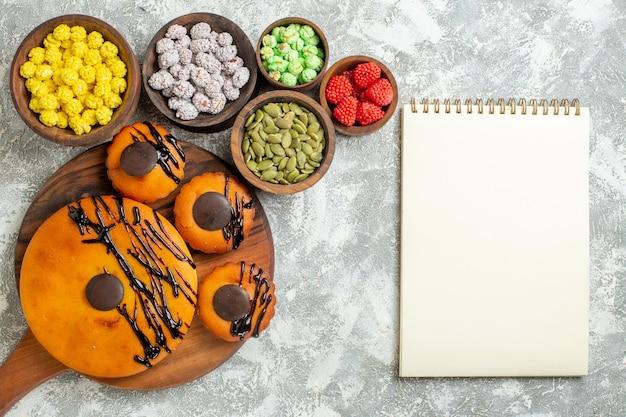 Vista de cima bolos saborosos com cobertura de chocolate e doces na superfície branca bolo torta de biscoito de cacau bolo de sobremesa biscoitos doces