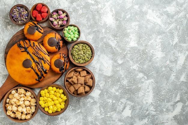 Vista de cima bolos saborosos com cobertura de chocolate e doces na superfície branca bolo torta de biscoito de cacau sobremesa biscoito doce
