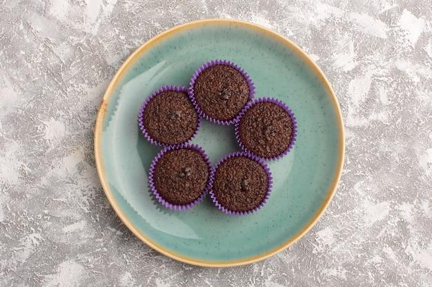 Vista de cima brownies deliciosos dentro da placa verde no fundo claro bolo de chocolate doce massa