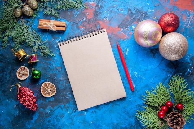 Vista de cima caderno lápis pinheiro galhos cones brinquedos de árvore de natal na superfície azul