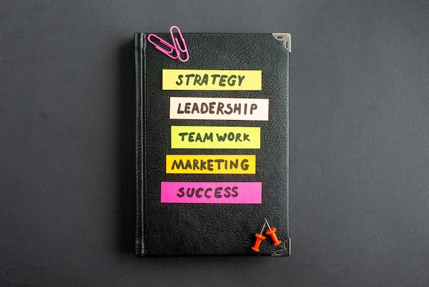 Vista de cima caderno preto com notas de negócios em adesivos em fundo escuro estratégia negócios marketing trabalho trabalho em equipe escritório liderança sucesso trabalho