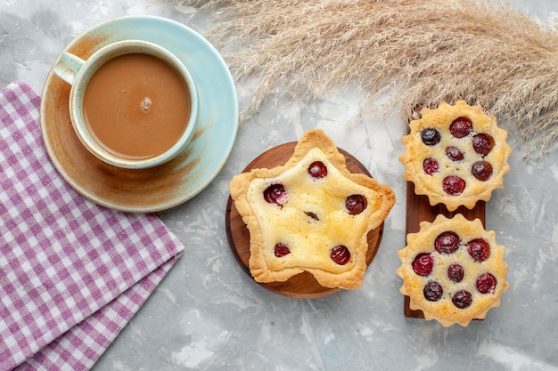 Vista de cima, café com leite com bolinhos na mesa clara, biscoito doce açúcar, foto colorida de frutas