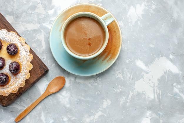 Vista de cima, café com leite com um pequeno bolo de frutas na mesa de luz, bolo de biscoitos doce açúcar