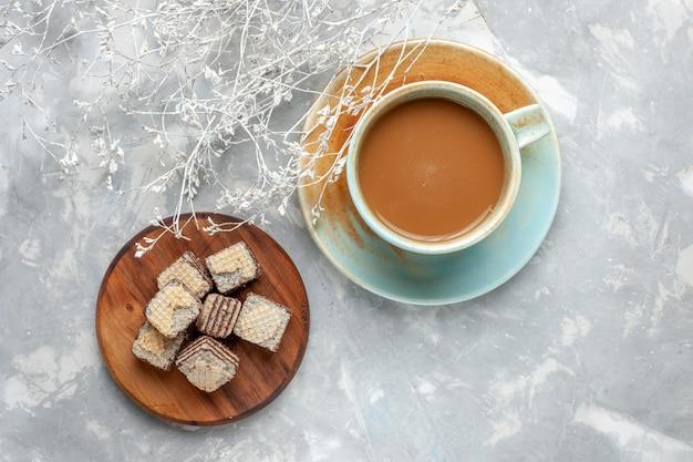 Vista de cima, café com leite com waffles de chocolate na mesa cinza, biscoito doce e bolo de açúcar