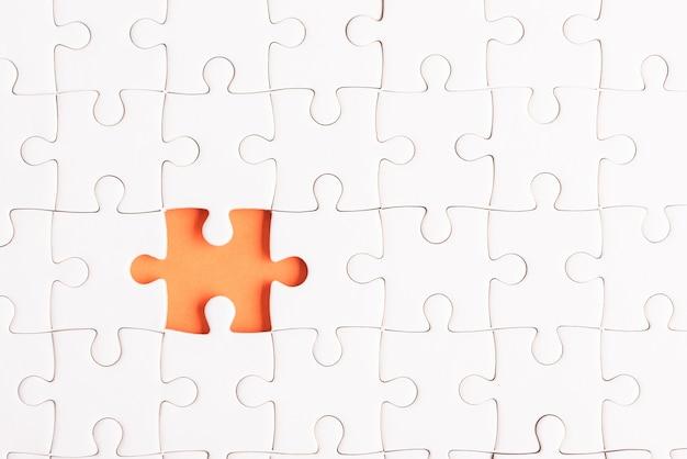 Vista de cima, camada plana de papel branco, textura de jogo de quebra-cabeça incompleta ou peça faltando