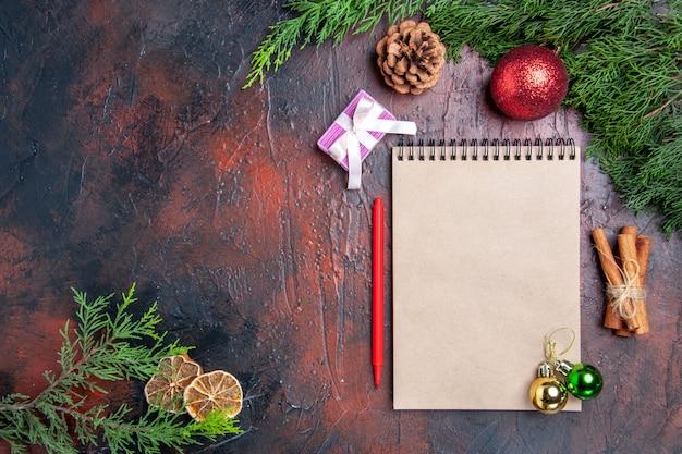 Vista de cima caneta vermelha um caderno pinheiro galhos de árvore de natal brinquedos bola de canela paus de canela rodelas de limão seco na superfície vermelha escura espaço livre foto de natal