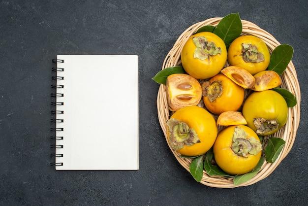 Vista de cima caqui doce fresco dentro de uma cesta em mesa escura com frutas maduras