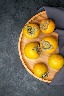Vista de cima caqui fresco frutas maduras doces na mesa escura frutas maduras maduras