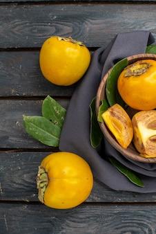 Vista de cima caquis doce doce em piso de madeira com frutas maduras