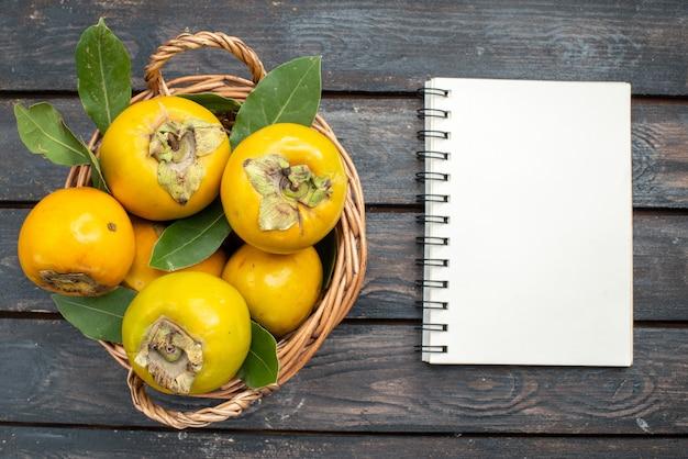 Vista de cima caquis frescos dentro da cesta na mesa de madeira, frutas maduras maduras