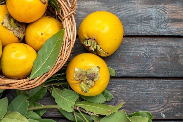 Vista de cima caquis frescos dentro de uma cesta em piso de madeira com frutas maduras