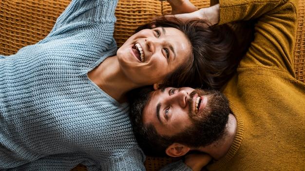 Vista de cima casal sorridente deitado junto
