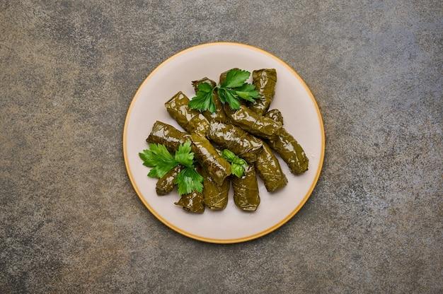 Vista de cima caseiro deliciosas folhas de uva recheadas dolma com salsa em prato de cerâmica sobre madeira enferrujada