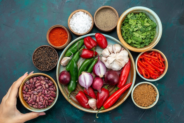 Vista de cima cebolas e alhos com pimentão vermelho, feijão, verduras, mesa escura, ingrediente alimentar, refeição, produto, alimento