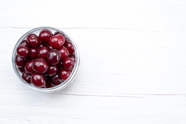Vista de cima cereja azeda vermelha fresca inteira e suave na mesa clara fruta cor fresca azeda doce suculenta