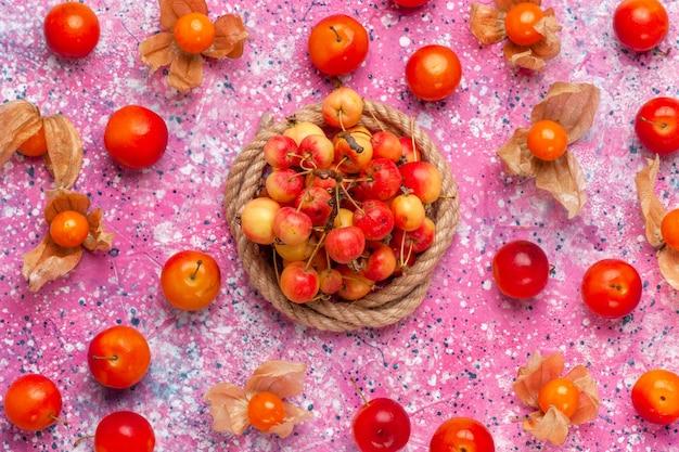 Vista de cima cerejas doces frescas com ameixas na mesa rosa claro.