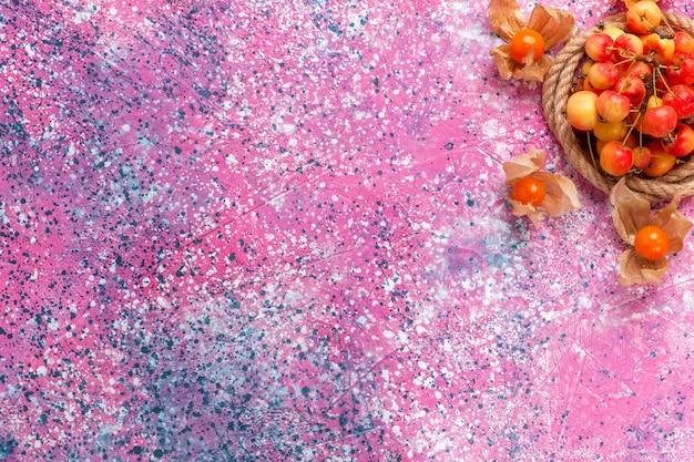 Vista de cima cerejas doces frescas com cordas na mesa rosa claro.